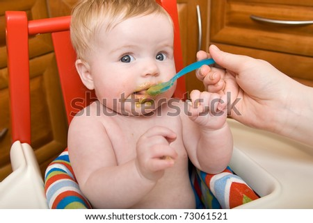 Baby Girl Eating Food For the First Time - stock photo