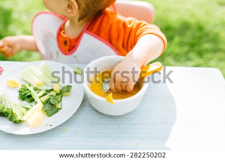 Baby girl eating her lunch in the garden outside in summer - stock photo
