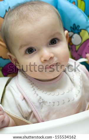 Baby girl eating in highchair  - stock photo