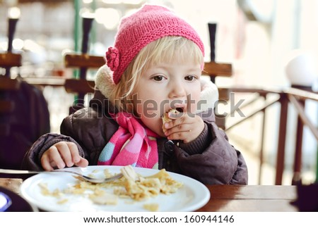 baby girl eating in outdoor cafe