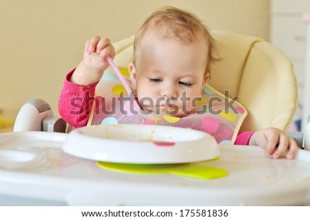 baby girl eating with spoon  - stock photo