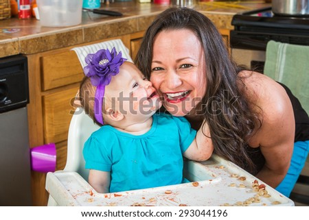 Baby girl gives her mother a kiss in the kitchen - stock photo