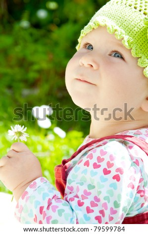 Baby girl holding little flower, in the garden - stock photo