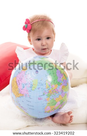 Baby girl holding world ball and sitting on fluffy blanket - stock photo