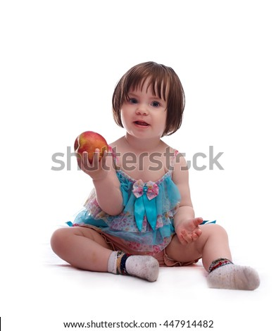 baby girl in a colorful dress isolated on a white background playing with red apple  - stock photo