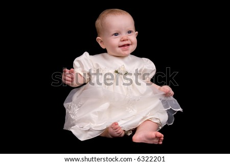 Baby girl in a white dress with ribbon isolated over black