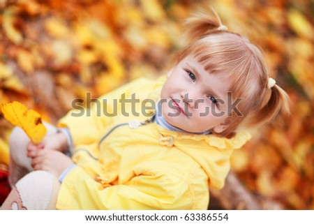 Baby girl in autumn leaves