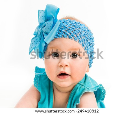 baby girl in blue decoration on the head and dress on white background close-up - stock photo