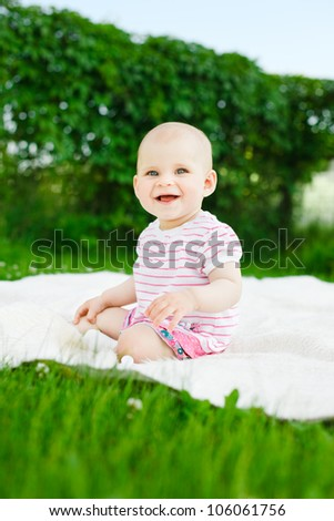 baby girl in dress sitting on green grass outdoors in soft lighting - stock photo