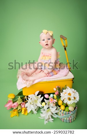 Baby girl in Easter outfit with Easter Eggs, and tulip flowers, sitting in a yellow cart - stock photo