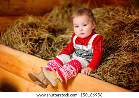 baby girl in fashion autumn clothes sitting on a hay  - stock photo