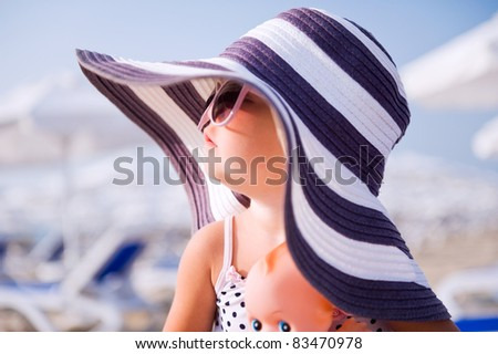 Baby girl in hat and sun glasses on the beach - stock photo