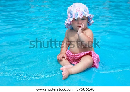 baby girl in hat sitting waterpool - stock photo