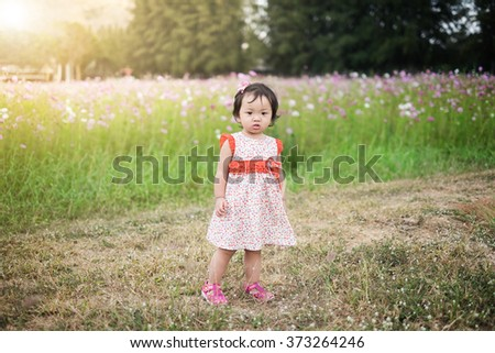 Baby girl in pink dress in the garden full of flowers - stock photo