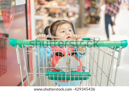 Baby girl in shopping cart alone in supermarket; Baby girl waiting parent in shopping cart.