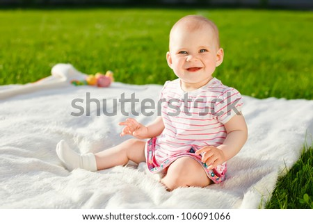 baby girl in striped dress and socks sitting and smiling on a white plaid outdoors in sunlight - stock photo