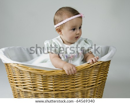 Baby Girl in Wicker Container Against Background.