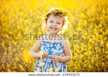 Baby girl in wreath smiling in field