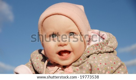 baby girl is delighted with something, looks in camera - stock photo