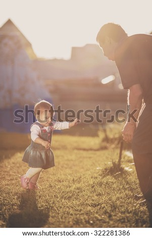 Baby girl is doing her first steps. Cute little girl is learning to walk and going to her grandfather in a sunny garden. Happy childhood concept. - stock photo