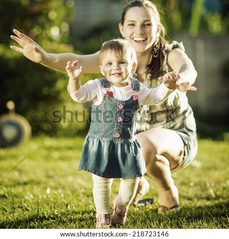 Baby girl is doing her first steps with mothers help. Cute little girl learns to walk with her young mom helping her in the sunny garden outdoors. Happy childhood and motherhood concept. Instagram  - stock photo