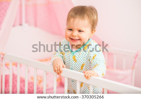 Baby Girl Is Just Standing In Bed In Baby Room