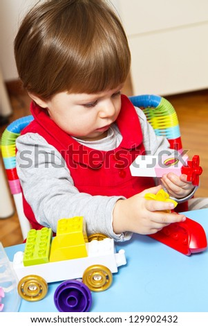 baby girl is playing with building bricks - stock photo