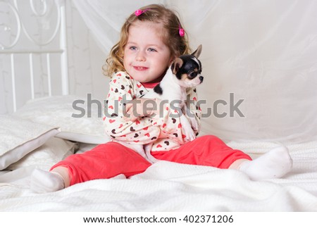 Baby girl is sitting on bed at home with dog - stock photo