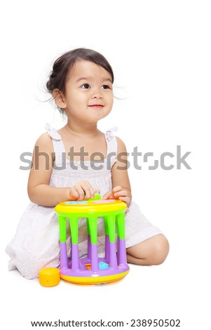 Baby girl is sitting with a colorful box shape matching toy isolated on white background - stock photo
