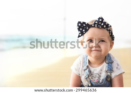 Baby girl is smiling and sitting on a beach near sea in jeans. - stock photo