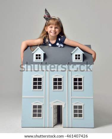 Baby Girl Kid playing with doll house sitting on a floor in play room at home or kindergarten happy smiling on gray background