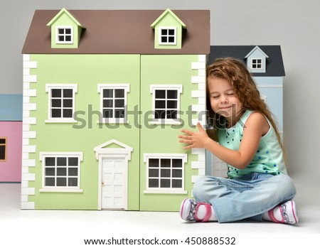 Baby Girl Kid playing with doll house sitting on a floor in play room at home or kindergarten with closed eyes listening and waiting for surprise