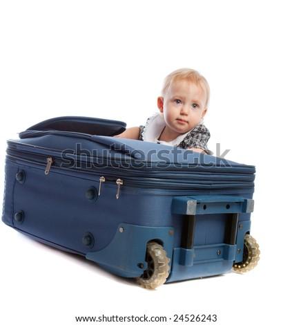 Baby girl kneeling behind large suitcase - stock photo