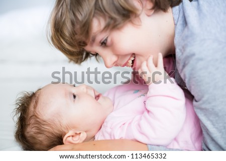 Baby girl laughing to her brother - stock photo
