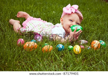 Baby girl laying in the grass with an assortment of colored Easter eggs - stock photo