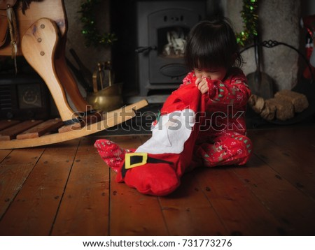 Baby girl looking for her gift in santa's sock on floor