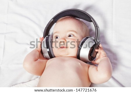 Baby girl lying down listening to music with wireless headphones. Close-up.