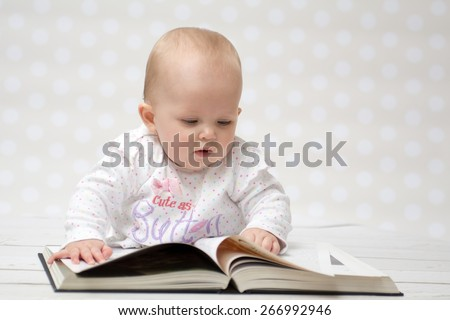 Baby girl lying on the belly reading a book - stock photo