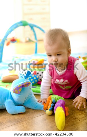 Baby girl (9 months) playing with soft toys at home. Toys are property released. - stock photo