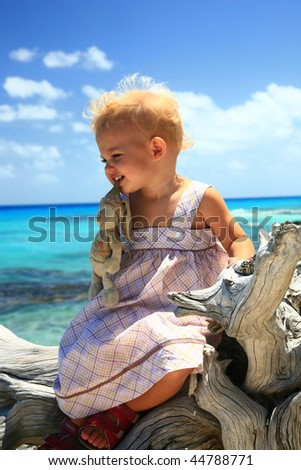 baby girl on a dead tree at tropical beach