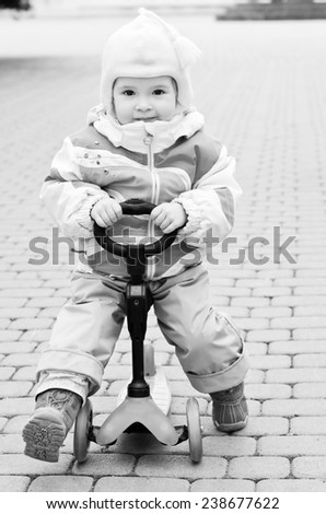 baby girl on scooter in the park  ( black and white ) - stock photo