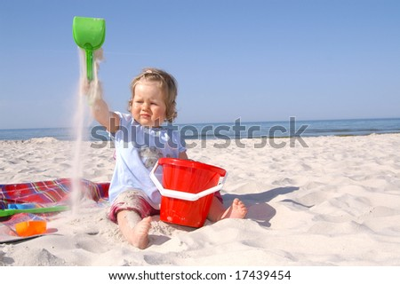 baby girl on the beach and blue sky