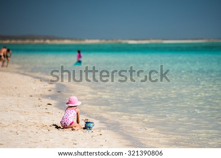baby girl on the beach in crystal water paradise background