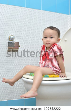baby girl on the toilet modern style. - stock photo