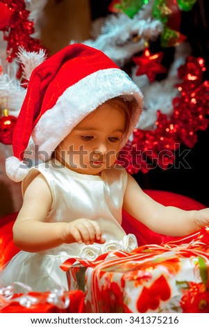 Baby girl opens her first Christmas gift. New year. Christmas mood. - stock photo