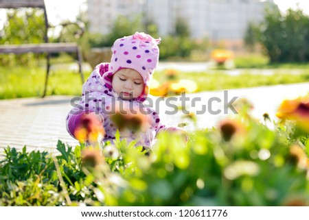 baby girl picking flowers in the park - stock photo