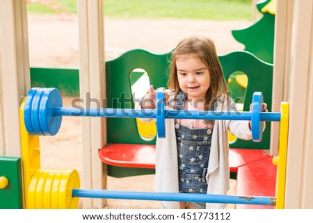 Baby girl playing at the playground in the park - stock photo