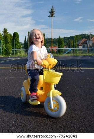 baby girl playing on motorbike - stock photo