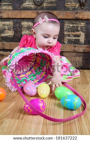 Baby girl playing with a basket filled with easter eggs