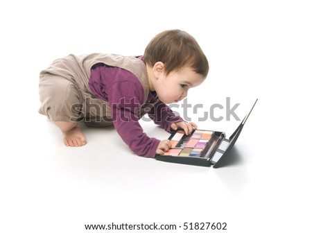 Baby girl playing with a cosmetic box - stock photo